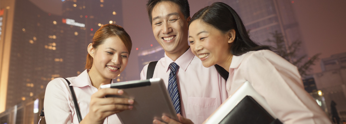 smiling businesspeople enjoying a tablet